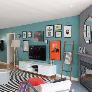 Inspiration pour une salle de séjour bohème de taille moyenne et fermée avec un mur vert, un sol en bois clair, une cheminée d'angle, un manteau de cheminée en plâtre, un téléviseur fixé au mur et un sol beige.