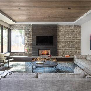 Diseño de sala de estar abierta, contemporánea, grande, con paredes grises, suelo de madera oscura, chimenea tradicional, marco de chimenea de metal y televisor colgado en la pared