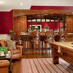 ボストンの広いトラディショナルスタイルのおしゃれな独立型ファミリールーム (ゲームルーム、赤い壁、無垢フローリング、標準型暖炉、木材の暖炉まわり、テレビなし、茶色い床) の写真