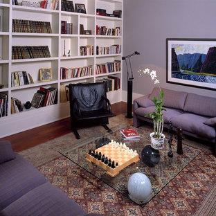 Immagine di un soggiorno tradizionale di medie dimensioni e chiuso con libreria, pareti viola, parquet scuro, nessun camino, nessuna TV e pavimento marrone