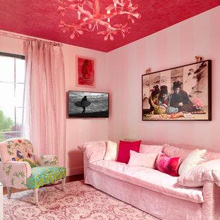 Idée de décoration pour une salle de séjour bohème avec un mur rose et un téléviseur fixé au mur.