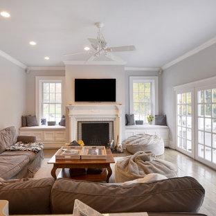 ニューヨークの大きいヴィクトリアン調のおしゃれな独立型ファミリールーム (グレーの壁、濃色無垢フローリング、標準型暖炉、レンガの暖炉まわり、壁掛け型テレビ) の写真