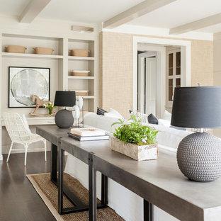 Immagine di un ampio soggiorno classico aperto con pareti beige, parquet scuro, camino classico, cornice del camino in pietra e TV a parete