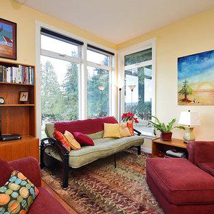 Ispirazione per un soggiorno chic di medie dimensioni e aperto con libreria, pareti gialle, parquet chiaro e parete attrezzata