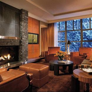 バンクーバーのコンテンポラリースタイルのおしゃれなファミリールーム (石材の暖炉まわり) の写真