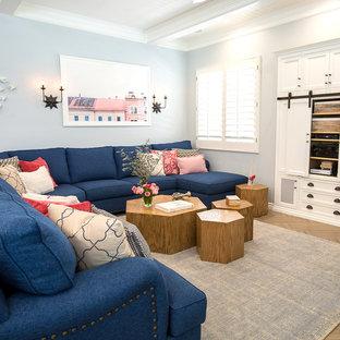 ロサンゼルスの広いトランジショナルスタイルのおしゃれなオープンリビング (青い壁、セラミックタイルの床、コーナー設置型暖炉、木材の暖炉まわり、壁掛け型テレビ、茶色い床) の写真
