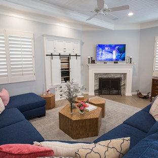 Cette photo montre une grande salle de séjour chic ouverte avec un mur bleu, un sol en carrelage de céramique, une cheminée d'angle, un manteau de cheminée en bois, un téléviseur fixé au mur et un sol marron.