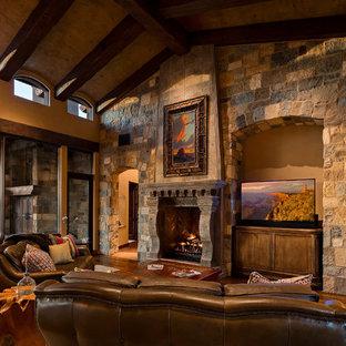 Modelo de sala de estar cerrada, de estilo americano, con suelo de madera en tonos medios, chimenea tradicional, marco de chimenea de piedra, paredes beige y pared multimedia