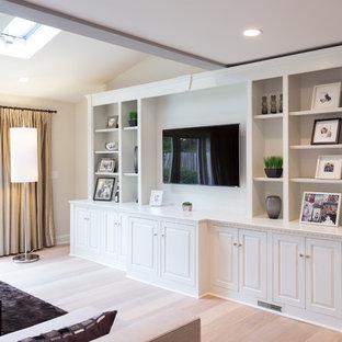 Esempio di un grande soggiorno moderno aperto con pareti beige, parquet chiaro, camino bifacciale, cornice del camino in pietra e parete attrezzata