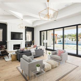 Foto di un ampio soggiorno tradizionale aperto con sala giochi, pareti nere, parquet chiaro, camino classico, cornice del camino in legno, TV a parete e pavimento beige