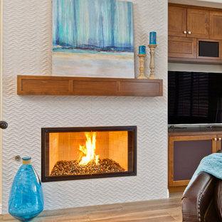 サンディエゴの中くらいのビーチスタイルのおしゃれなオープンリビング (ベージュの壁、セラミックタイルの床、横長型暖炉、タイルの暖炉まわり、埋込式メディアウォール) の写真