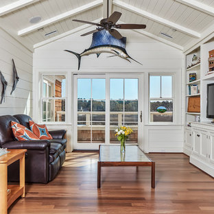 Beach style enclosed medium tone wood floor and brown floor family room photo in Atlanta with white walls, no fireplace and a media wall