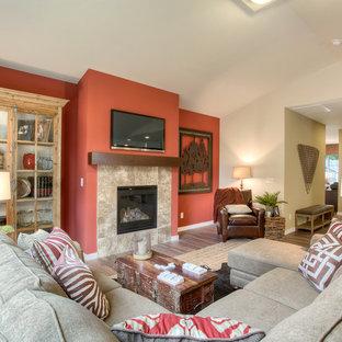 Immagine di un grande soggiorno tradizionale aperto con pareti rosse, camino classico, cornice del camino piastrellata, TV a parete e parquet scuro