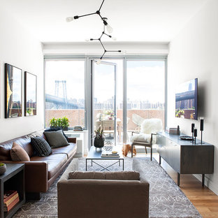 Example of an urban light wood floor family room design in New York with white walls and a wall-mounted tv