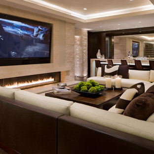 This is an example of a contemporary family and games room in Denver with a home bar, beige walls, a ribbon fireplace, a stone fireplace surround and a wall mounted tv.