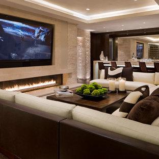 Foto de sala de estar con barra de bar contemporánea con paredes beige, chimenea lineal, marco de chimenea de piedra y televisor colgado en la pared