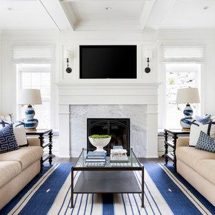 Ejemplo de sala de estar clásica renovada con paredes blancas, chimenea tradicional, marco de chimenea de piedra y televisor colgado en la pared