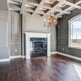 オースティンの中サイズのヴィクトリアン調のおしゃれな独立型ファミリールーム (グレーの壁、磁器タイルの床、標準型暖炉、タイルの暖炉まわり) の写真