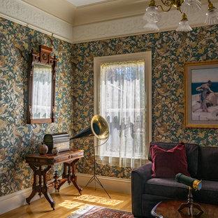 ボストンのヴィクトリアン調のおしゃれなファミリールーム (マルチカラーの壁、無垢フローリング、茶色い床) の写真