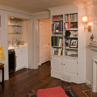 Inspiration pour une petite salle de séjour avec une bibliothèque ou un coin lecture traditionnelle fermée avec un mur blanc, un sol en bois brun, une cheminée standard, un manteau de cheminée en plâtre, aucun téléviseur et un sol marron.