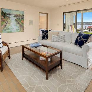 シアトルの大きいミッドセンチュリースタイルのおしゃれなファミリールーム (黄色い壁、テラコッタタイルの床、標準型暖炉、レンガの暖炉まわり) の写真