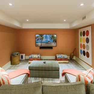 ボストンのビーチスタイルのおしゃれな独立型ファミリールーム (オレンジの壁、カーペット敷き、壁掛け型テレビ、グレーの床) の写真