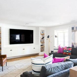 Ejemplo de sala de estar costera, de tamaño medio, con paredes blancas, suelo de madera clara, pared multimedia y suelo beige