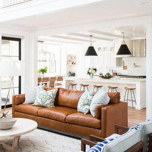 Ispirazione per un soggiorno stile marinaro di medie dimensioni e aperto con pareti bianche, pavimento in legno massello medio e camino classico
