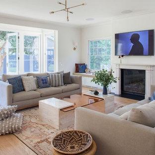Idee per un soggiorno tradizionale di medie dimensioni e aperto con pareti bianche, parquet chiaro, camino classico, cornice del camino in intonaco e TV a parete