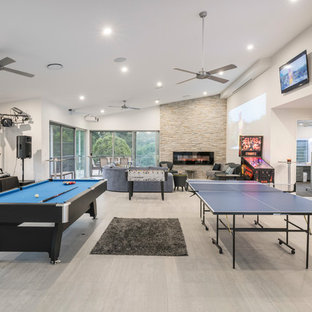 Design ideas for a contemporary open concept family room in Brisbane with a game room, white walls, light hardwood floors, a ribbon fireplace, a metal fireplace surround, a wall-mounted tv and beige floor.