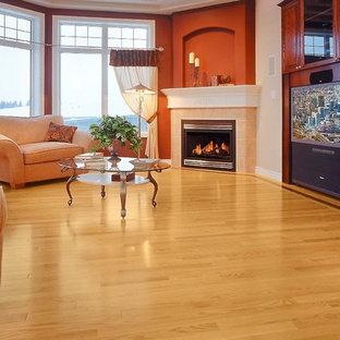 他の地域の大きいトラディショナルスタイルのおしゃれな独立型ファミリールーム (ベージュの壁、淡色無垢フローリング、標準型暖炉、金属の暖炉まわり、埋込式メディアウォール、ベージュの床) の写真