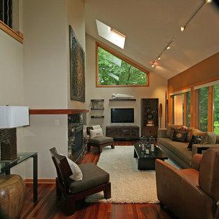 Ispirazione per un soggiorno etnico di medie dimensioni e aperto con pareti beige, camino classico, cornice del camino piastrellata, TV a parete e parquet scuro