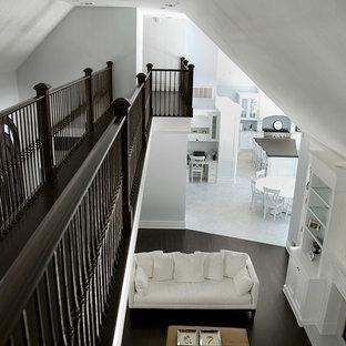 他の地域の中サイズのビーチスタイルのおしゃれなファミリールーム (白い壁、濃色無垢フローリング、標準型暖炉、漆喰の暖炉まわり、黒い床) の写真
