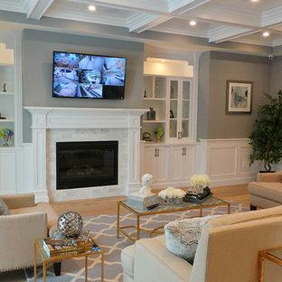 Diseño de sala de estar abierta, de estilo americano, grande, con paredes grises, suelo de madera clara, chimenea tradicional, marco de chimenea de baldosas y/o azulejos y televisor colgado en la pared