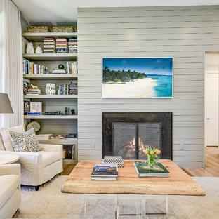 Inspiration pour une salle de séjour avec une bibliothèque ou un coin lecture marine ouverte avec un mur gris, une cheminée standard, un téléviseur fixé au mur et un sol en bois clair.