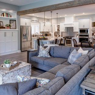 Cette image montre une grande salle de séjour rustique ouverte avec une cheminée standard, aucun téléviseur et un sol marron.