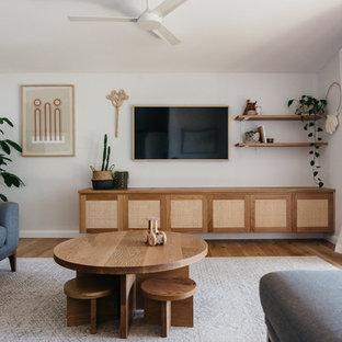 セントラルコーストの中サイズのビーチスタイルのおしゃれなファミリールーム (白い壁、淡色無垢フローリング、暖炉なし、壁掛け型テレビ) の写真