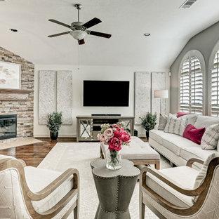 ヒューストンの中くらいのトランジショナルスタイルのおしゃれな独立型ファミリールーム (白い壁、コーナー設置型暖炉、石材の暖炉まわり、壁掛け型テレビ、茶色い床、三角天井、濃色無垢フローリング) の写真