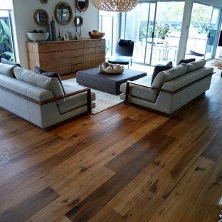 Ejemplo de sala de estar abierta, moderna, grande, sin chimenea y televisor, con paredes blancas y suelo de madera en tonos medios