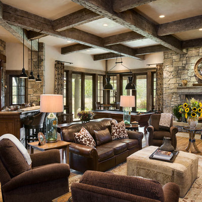 Family room - rustic open concept medium tone wood floor family room idea in Other with beige walls, a standard fireplace and a stone fireplace