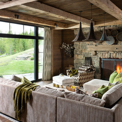 Large mountain style open concept medium tone wood floor and brown floor family room photo in Other with brown walls, a standard fireplace and a stone fireplace