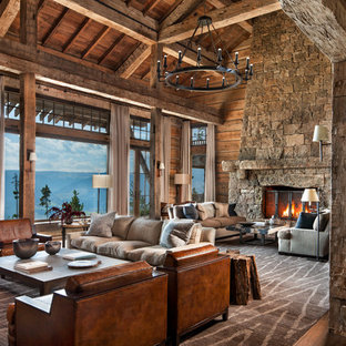 Неиссякаемый источник вдохновения для домашнего уюта: огромная открытая гостиная комната в стиле рустика с коричневыми стенами, паркетным полом среднего тона, стандартным камином, фасадом камина из камня и коричневым полом