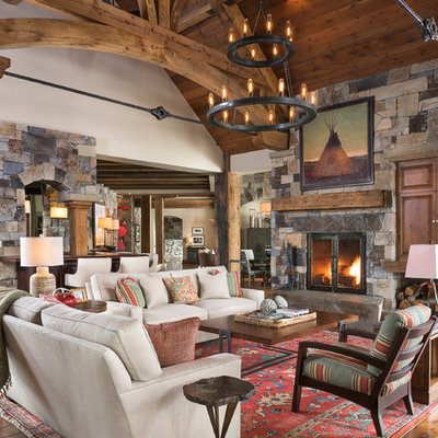 Inspiration for a rustic medium tone wood floor family room remodel in Other with a standard fireplace, a stone fireplace and a concealed tv