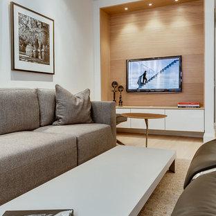 Ejemplo de sala de estar abierta, minimalista, pequeña, con paredes blancas, suelo de madera clara y pared multimedia