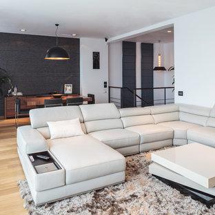 Idées déco pour une salle de séjour contemporaine ouverte avec un mur noir et un sol en bois clair.