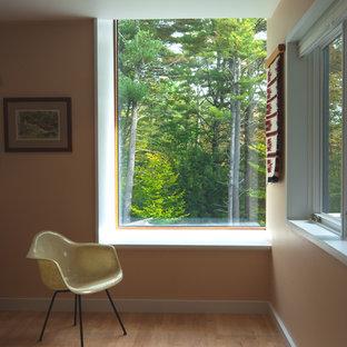 Idée de décoration pour une salle de séjour minimaliste fermée avec un mur orange et un sol en bois clair.