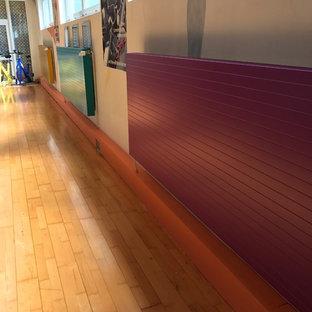 Foto di una piccola palestra multiuso mediterranea con pareti bianche, pavimento in legno massello medio e pavimento marrone