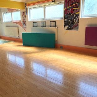 Idee per una piccola palestra multiuso mediterranea con pareti bianche, pavimento in legno massello medio e pavimento marrone