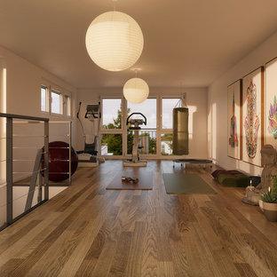 Multifunktionaler, Mittelgroßer Asiatischer Fitnessraum mit weißer Wandfarbe, braunem Holzboden und braunem Boden in Stuttgart