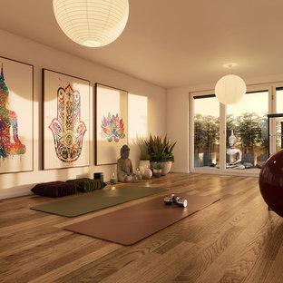 Esempio di uno studio yoga etnico di medie dimensioni con pareti bianche, pavimento in legno massello medio e pavimento marrone